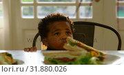 Купить «Front view of cute little black boy sitting on chair at dining table in a comfortable home 4k», видеоролик № 31880026, снято 19 октября 2018 г. (c) Wavebreak Media / Фотобанк Лори