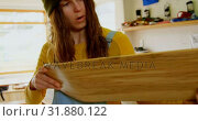 Купить «Front view of young caucasian woman examining skateboard deck in a workshop 4k», видеоролик № 31880122, снято 16 октября 2018 г. (c) Wavebreak Media / Фотобанк Лори