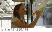 Купить «Side view of young caucasian businesswoman planning and working on glass wall of modern office 4k», видеоролик № 31880178, снято 13 октября 2018 г. (c) Wavebreak Media / Фотобанк Лори