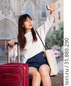 Купить «Enthusiastic chinese female tourist making selfie on the background of landmark», фото № 31880290, снято 18 августа 2019 г. (c) Яков Филимонов / Фотобанк Лори