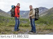 Купить «Two backpackers hiking in mountains. Senior and young adult men looking at camera», фото № 31880322, снято 17 июля 2015 г. (c) Кекяляйнен Андрей / Фотобанк Лори