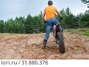 Купить «Mototrial rider standing with motorcycle in sand. Extreme sports on motorcross motorbike. Rear view, copyspace», фото № 31880378, снято 20 июля 2019 г. (c) Кекяляйнен Андрей / Фотобанк Лори