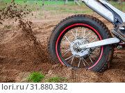 Купить «Rotating rear wheel of cross-country motorcycle with flying mud from tire», фото № 31880382, снято 20 июля 2019 г. (c) Кекяляйнен Андрей / Фотобанк Лори