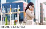 Купить «smiling asian woman calling on smartphone in city», видеоролик № 31880462, снято 21 июля 2019 г. (c) Syda Productions / Фотобанк Лори