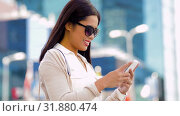Купить «asian woman in sunglasses using smartphone in city», видеоролик № 31880474, снято 21 июля 2019 г. (c) Syda Productions / Фотобанк Лори