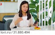 Купить «asian woman with smartphone at cafe or coffee shop», видеоролик № 31880494, снято 21 июля 2019 г. (c) Syda Productions / Фотобанк Лори