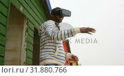 Купить «Side view of young black man gesturing while using virtual reality headset at beach hut 4k», видеоролик № 31880766, снято 14 ноября 2018 г. (c) Wavebreak Media / Фотобанк Лори