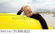 Купить «Front view of old caucasian woman holding surfboard at beach 4k», видеоролик № 31880822, снято 6 ноября 2018 г. (c) Wavebreak Media / Фотобанк Лори