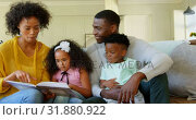 Купить «Front view of black family reading story book in living room 4k», видеоролик № 31880922, снято 7 ноября 2018 г. (c) Wavebreak Media / Фотобанк Лори