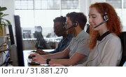 Купить «Side view of young cool mixed-race call center team calling and sitting at desk of modern office 4k», видеоролик № 31881270, снято 6 октября 2018 г. (c) Wavebreak Media / Фотобанк Лори