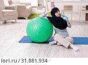Купить «Young woman in hijab doing exercises at home», фото № 31881934, снято 18 марта 2019 г. (c) Elnur / Фотобанк Лори