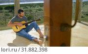 Купить «Front view of caucasian man playing guitar at porch of beach house 4k», видеоролик № 31882398, снято 22 июня 2018 г. (c) Wavebreak Media / Фотобанк Лори