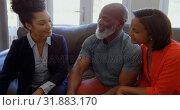 Купить «Mixed race female real estate agent discussing over property with mature couple at home 4k», видеоролик № 31883170, снято 7 ноября 2018 г. (c) Wavebreak Media / Фотобанк Лори