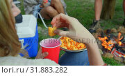 Купить «Woman eating food while sitting near bonfire in the forest 4k», видеоролик № 31883282, снято 12 октября 2018 г. (c) Wavebreak Media / Фотобанк Лори