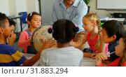 Купить «Caucasian male teacher teaching his kids about globe in classroom 4k», видеоролик № 31883294, снято 10 ноября 2018 г. (c) Wavebreak Media / Фотобанк Лори
