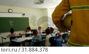 Купить «Firefighter walking in classroom at school 4k», видеоролик № 31884378, снято 10 ноября 2018 г. (c) Wavebreak Media / Фотобанк Лори
