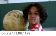 Купить «Front view of African American schoolboy with globe in a classroom at school 4k», видеоролик № 31887178, снято 10 ноября 2018 г. (c) Wavebreak Media / Фотобанк Лори