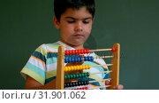 Caucasian boy learning mathematics with abacus against green board in classroom 4k. Стоковое видео, агентство Wavebreak Media / Фотобанк Лори