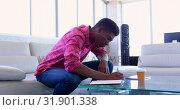 Купить «Handsome African american male executive writing on a diary in modern office 4k», видеоролик № 31901338, снято 18 ноября 2018 г. (c) Wavebreak Media / Фотобанк Лори