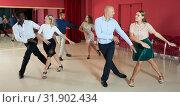 Купить «Active smiling people practicing lindy hop movements in dance class», фото № 31902434, снято 4 октября 2018 г. (c) Яков Филимонов / Фотобанк Лори