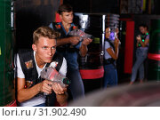 Купить «Young guy holding colored laser guns and took aim during laser tag game in labyrinth», фото № 31902490, снято 23 августа 2018 г. (c) Яков Филимонов / Фотобанк Лори