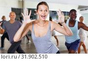 Cheerful people practicing vigorous lindy hop movements in dance class. Стоковое фото, фотограф Яков Филимонов / Фотобанк Лори