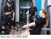 Athletic young people during functional workout with electric muscle stimulation in fitness gym. Стоковое фото, фотограф Яков Филимонов / Фотобанк Лори