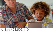 Купить «Front view of Caucasian male teacher teaching schoolboy on digital tablet in the classroom 4k», видеоролик № 31903110, снято 17 ноября 2018 г. (c) Wavebreak Media / Фотобанк Лори