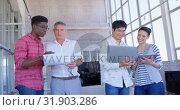 Купить «Multi-ethnic business people discussing over document and laptop in modern office 4k», видеоролик № 31903286, снято 18 ноября 2018 г. (c) Wavebreak Media / Фотобанк Лори