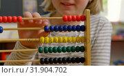 Mid section of Caucasian schoolgirl learning mathematics with abacus in the classroom 4k. Стоковое видео, агентство Wavebreak Media / Фотобанк Лори