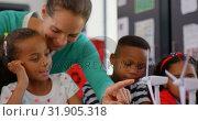 Купить «Front view of Caucasian female teacher teaching student about windmill in the classroom 4k», видеоролик № 31905318, снято 17 ноября 2018 г. (c) Wavebreak Media / Фотобанк Лори
