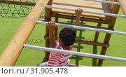 Купить «High angle view of African American schoolboy playing on horizontal ladder in school playground 4k», видеоролик № 31905478, снято 17 ноября 2018 г. (c) Wavebreak Media / Фотобанк Лори