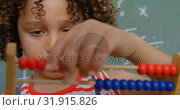Купить «Front view of mixed-race schoolgirl learning mathematics with abacus in a classroom at school 4k», видеоролик № 31915826, снято 17 ноября 2018 г. (c) Wavebreak Media / Фотобанк Лори