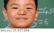 Купить «Close-up of Asian schoolboy standing against chalkboard in a classroom at school 4k», видеоролик № 31917654, снято 17 ноября 2018 г. (c) Wavebreak Media / Фотобанк Лори