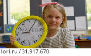 Купить «Front view of Caucasian schoolgirl with wall clock sitting at desk in classroom 4k», видеоролик № 31917670, снято 17 ноября 2018 г. (c) Wavebreak Media / Фотобанк Лори