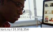Купить «Side view of African American male graphic designer working at desk in office 4k», видеоролик № 31918354, снято 18 ноября 2018 г. (c) Wavebreak Media / Фотобанк Лори