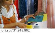 Купить «Front view of African American female fashion designer looking at cloth samples in workshop 4k», видеоролик № 31918802, снято 18 ноября 2018 г. (c) Wavebreak Media / Фотобанк Лори