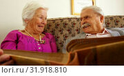 Front view of active Caucasian senior couple looking at photo album in nursing home 4k. Стоковое видео, агентство Wavebreak Media / Фотобанк Лори