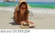 Купить «Front view of Caucasian woman in hat reading book on the beach 4k», видеоролик № 31919254, снято 12 ноября 2018 г. (c) Wavebreak Media / Фотобанк Лори