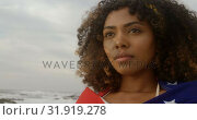 Купить «Front view of African American woman wrapped in American flag standing on the beach 4k», видеоролик № 31919278, снято 12 ноября 2018 г. (c) Wavebreak Media / Фотобанк Лори