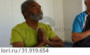 Купить «Front view of active mixed-race senior people performing yoga in fitness studio 4k », видеоролик № 31919654, снято 22 ноября 2018 г. (c) Wavebreak Media / Фотобанк Лори