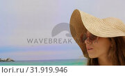 Купить « Front view of Caucasian woman in hat and sunglasses standing on the beach 4k», видеоролик № 31919946, снято 12 ноября 2018 г. (c) Wavebreak Media / Фотобанк Лори