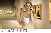 Купить «Woman with brochure looking at exposition», фото № 31919978, снято 22 сентября 2018 г. (c) Яков Филимонов / Фотобанк Лори