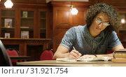 Купить «Man studying in the library 4k», видеоролик № 31921754, снято 8 ноября 2017 г. (c) Wavebreak Media / Фотобанк Лори