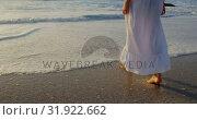Купить «Woman walking on beach during sunset 4k», видеоролик № 31922662, снято 12 декабря 2018 г. (c) Wavebreak Media / Фотобанк Лори
