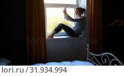 Купить «Beautiful woman taking selfie with mobile phone at home 4k», видеоролик № 31934994, снято 7 марта 2018 г. (c) Wavebreak Media / Фотобанк Лори