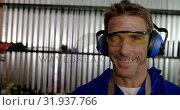 Купить «Male mechanic looking at camera in repair garage 4k», видеоролик № 31937766, снято 10 февраля 2019 г. (c) Wavebreak Media / Фотобанк Лори