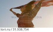 Купить «Woman waving american flag on the beach in the sunshine 4k», видеоролик № 31938754, снято 8 февраля 2019 г. (c) Wavebreak Media / Фотобанк Лори