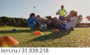 Купить «Female soccer players doing sit up exercises while captain gives training on soccer field. 4k», видеоролик № 31939218, снято 18 апреля 2019 г. (c) Wavebreak Media / Фотобанк Лори