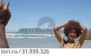 Купить «Young African american man taking pictures of woman with digital camera on the beach 4k», видеоролик № 31939326, снято 14 февраля 2019 г. (c) Wavebreak Media / Фотобанк Лори